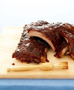 3 ingredient ribs on wood cutting board with sauce brush
