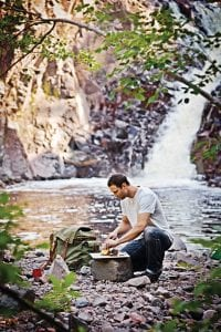 Epicurean cutting board being used by a hiker at the side of a lake