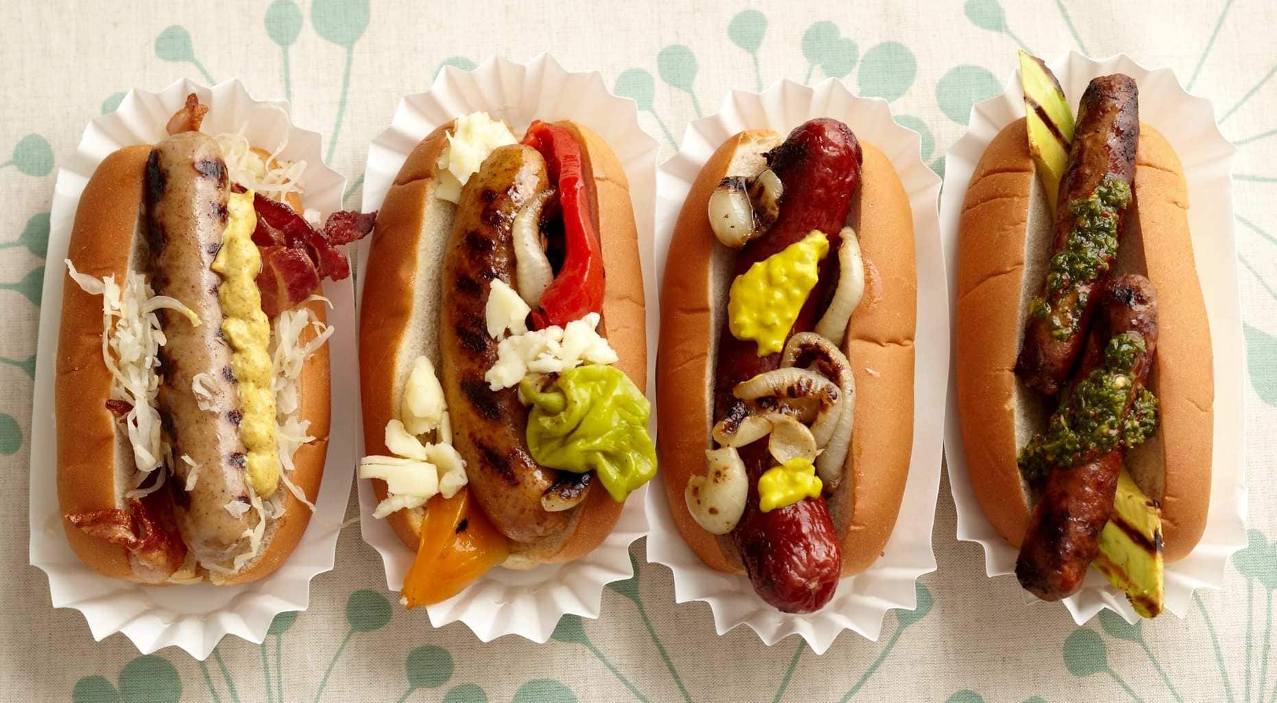 Overhead view of four fancy Hot Dogs in paper holders