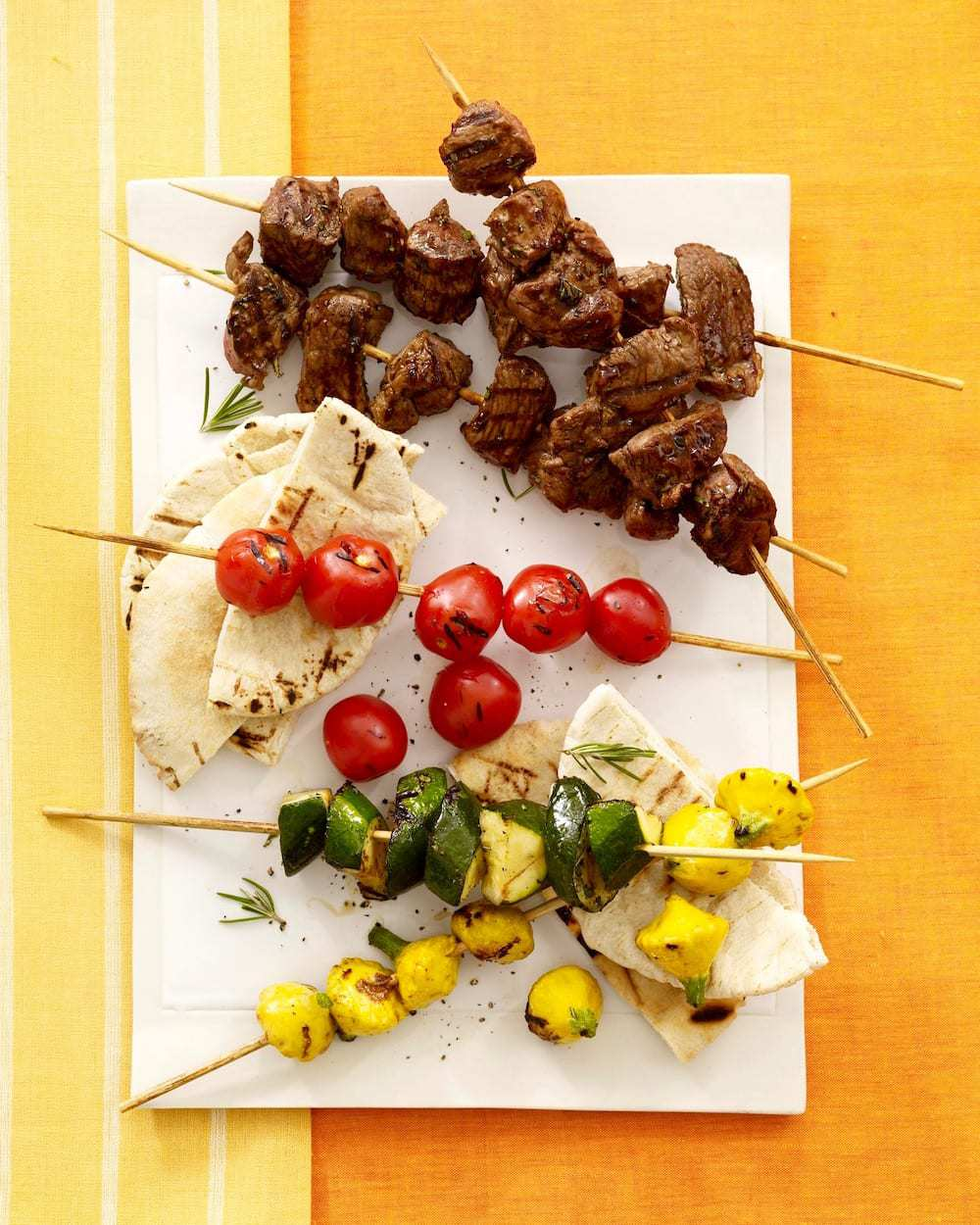 Lemon Herb Lamb And Vegetable Kabobs on white platter