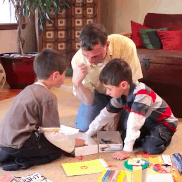 Close up of a father playing a board game with his young sons on the floor