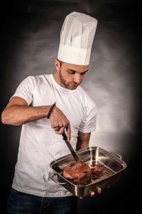 Man wearing white chef's hat cutting beef roast in roasting pan