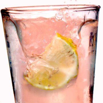 Pink summer lemonade with lemon in glass