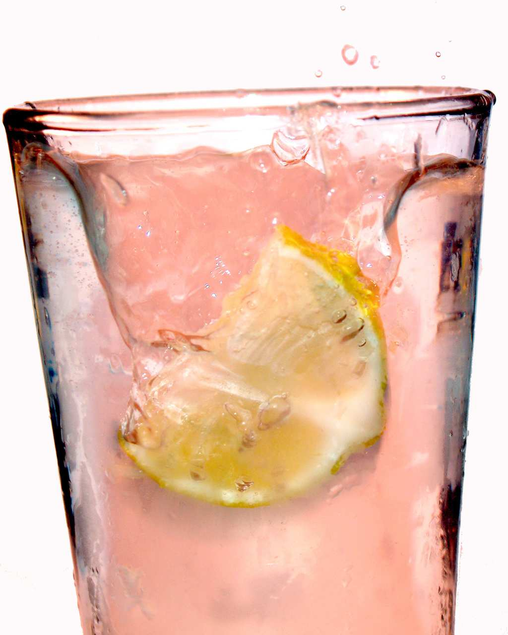 Pink summer lemonade with lemon in glass