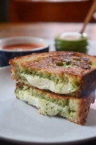 Pesto Mozzarella Grilled Cheese half sandwich recipe image