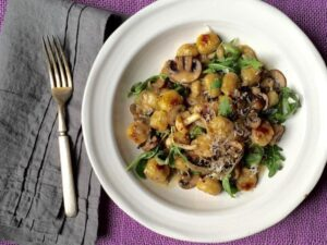 Close up of Easy Parmesan Mushroom Gnocchi on white plate resting on purple linen placemat