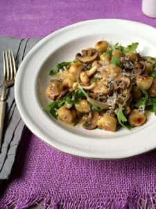 A plate of Easy Parmesan Mushroom Gnocchi with mushrooms and onions
