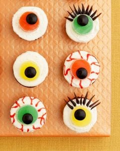 Close up of six Eerie Eyeball Cupcakes on orange surface