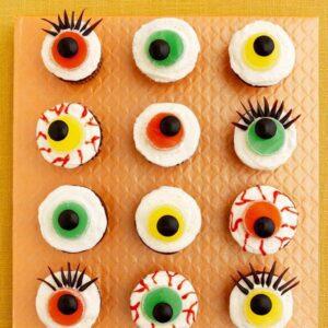 One dozen Eerie Eyeball Cupcakes on orange surface