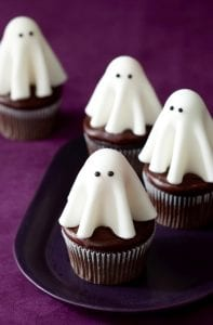 Floating ghost cupcakes on purple background