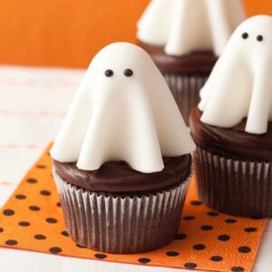 Close up of Floating ghost cupcakes on orange and black polka dot napkin