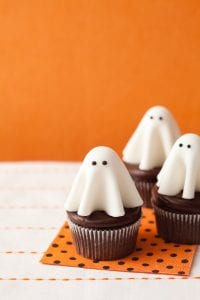 Floating ghost cupcakes on orange and black polka dot napkin