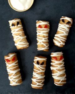 Close up of six pizza roll up mummy snacks with dipping suace