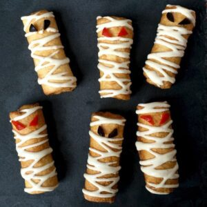 Close up of six pizza roll up mummy snacks