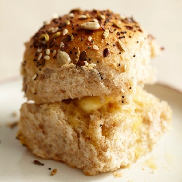 Close up of Single Dinner Roll with Savory Seed Topping on a white saucer