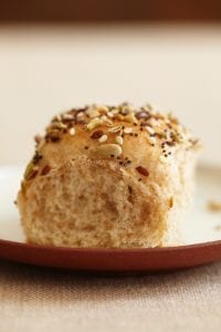 Single Dinner Roll with Savory Seed Topping on a white saucer