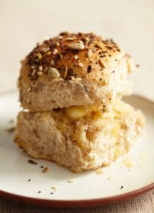 Single Dinner Roll with Savory Seed Topping sliced in half with butter