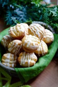 Orange Rolls with white icing in basket on brown surface