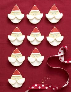 Santa face sugar cookies displayed iwth red and white polka dot ribbon and cookie crumbs