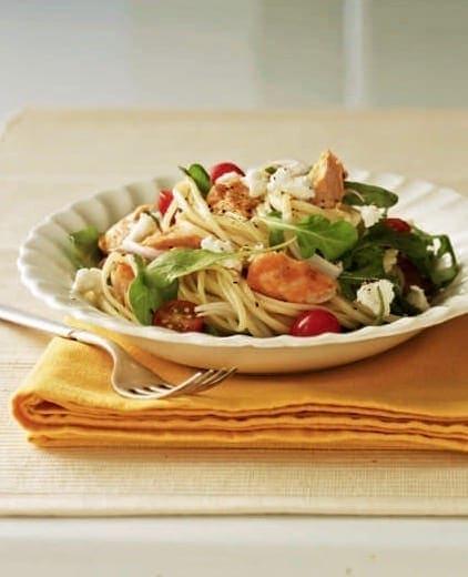 Warm salmon and arugula pasta salad in white bowl on yellow napkin