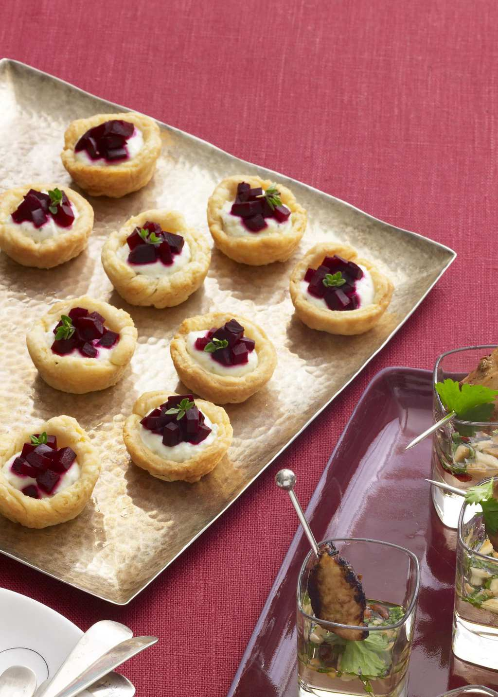 Beet and Farmer Cheese Tartlets on square plate w rose-colored background