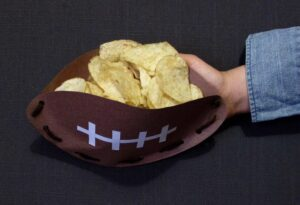 Handcrafted paper football snack bowl filled with chips