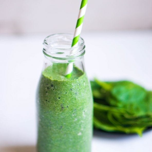 Green Goddess Smoothie recipe image with spinach leaves on the side