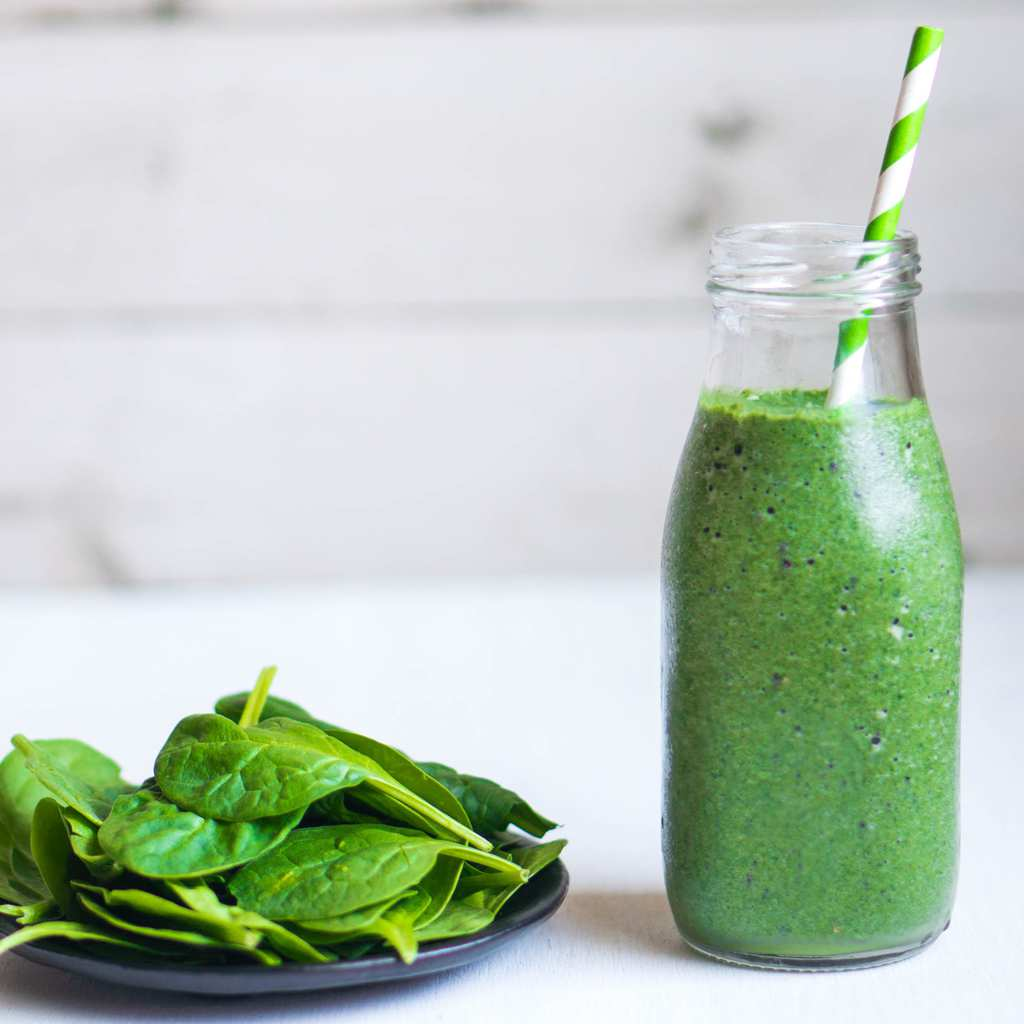 Green Goddess Smoothie in jar with straw with Spinach on plate