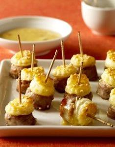 Posh Piggies recipe image on white platter with wooden toothpicks