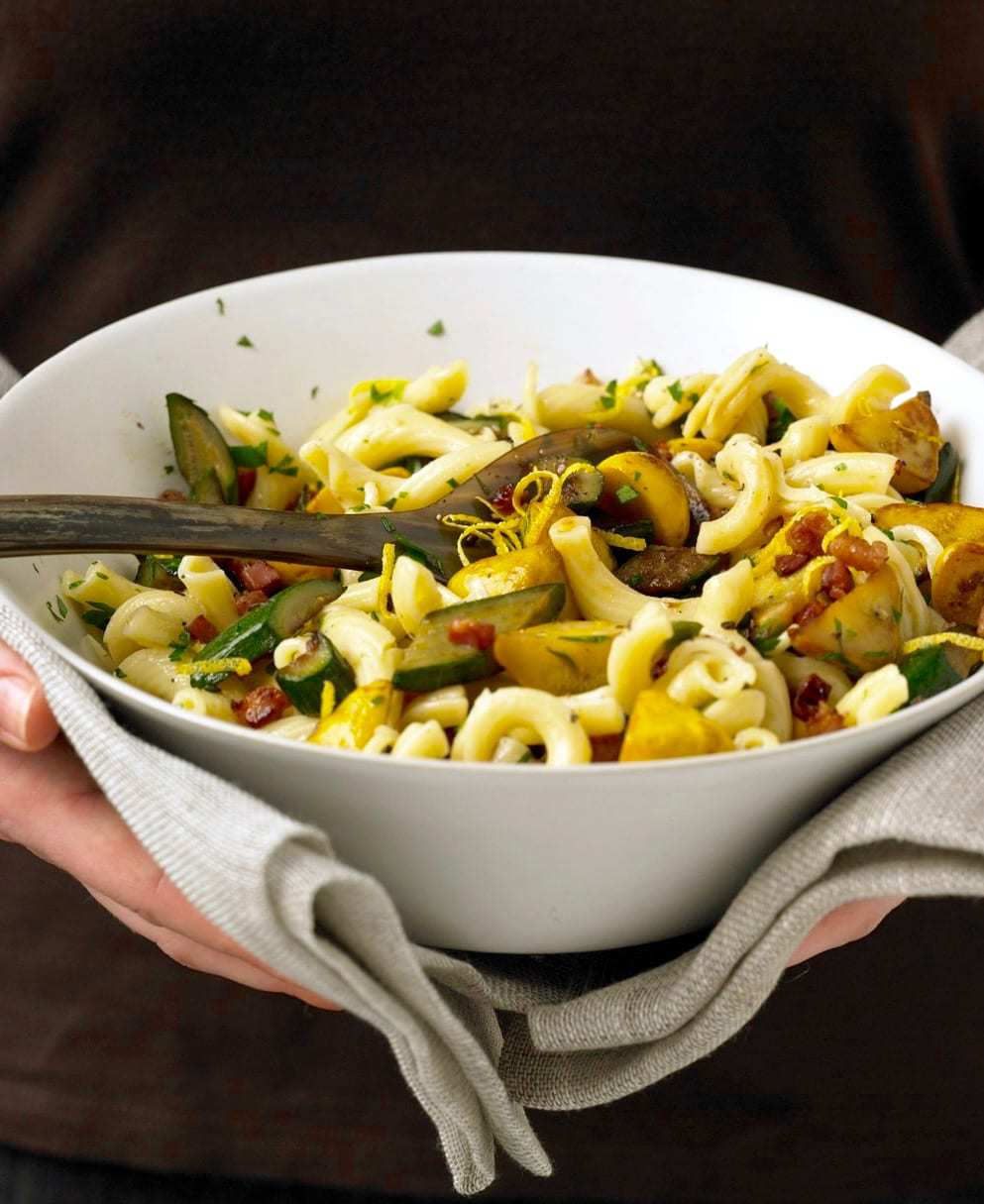 Squash and Pancetta pasta held in white bowl with linen napkin
