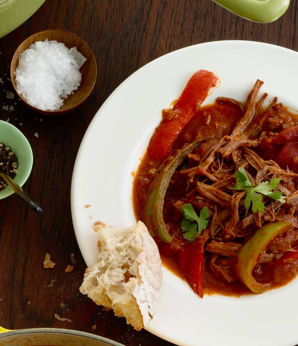 Ropa Vieja in white bowl with bread, salt and pepper on wooden table