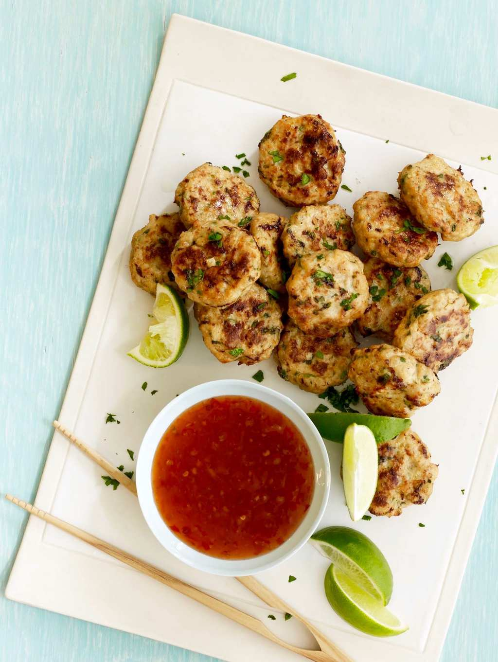 Ginger Thai Chicken Patties with sauce, limes and chopsticks overhead on white try and green background