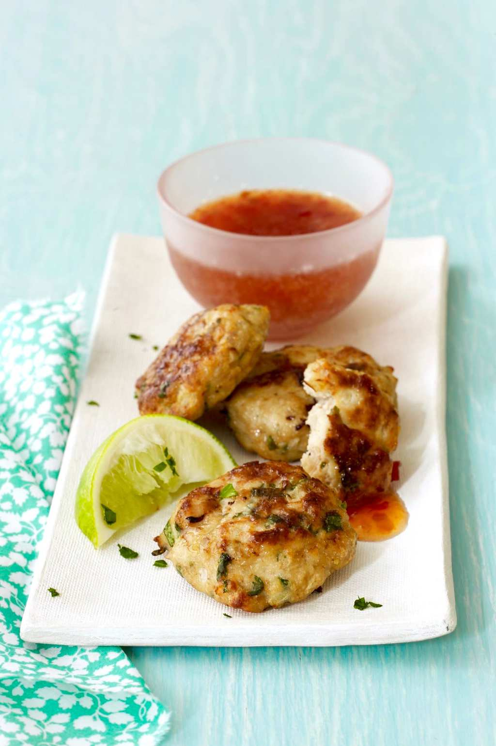 Ginger Thai Chicken Patties with sweet chili sauce on white plate with mint green background