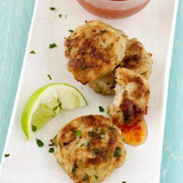 Overhead of Thai chicken patties on white platter with sauce