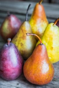 Various species of fresh pears on wood surface