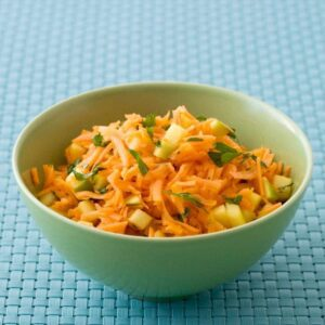 Shredded Carrot Salad recipe image in green bowl on blue surface