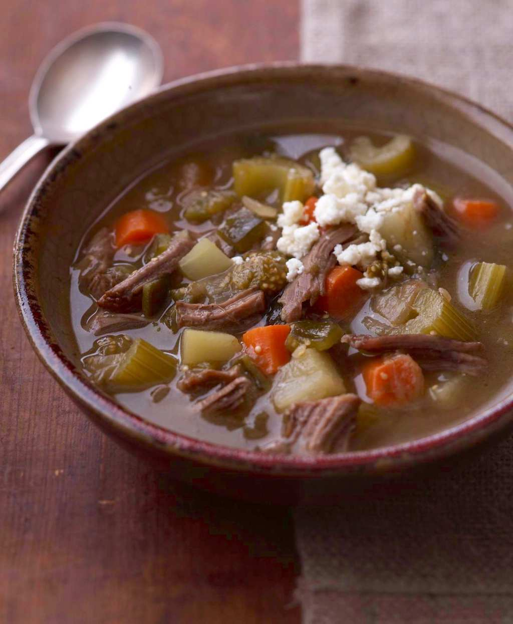 Mexican Tomatillo and Shredded Beef soup in bowl with spoon