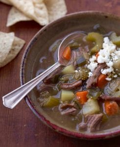 Mexican tomatillo and shredded beef soup in clay bowl