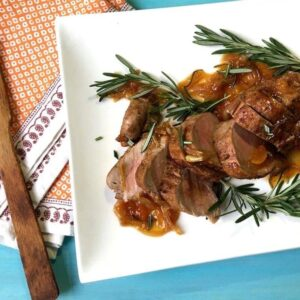Sliced Pork Tenderloin With Rosemary Apricot Sauce on white platter