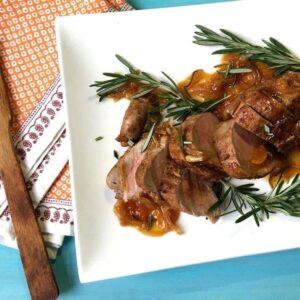 Sliced Pork Tenderloin With Rosemary Apricot Sauce on white platter