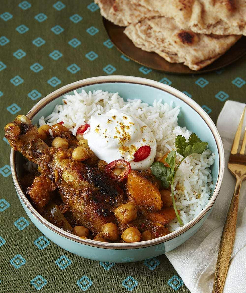 Curry Chicken Drumsticks with Chickpeas  served with rice and Yogurt in turquoise bowl with nann bread