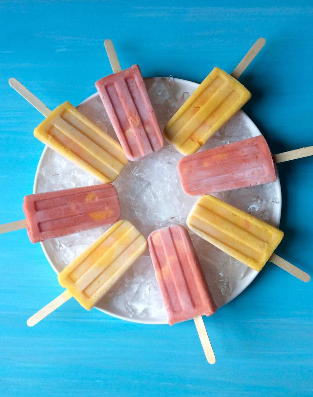 Halos Mandarins Frozen Smoothie Pops on ice with turquoise background
