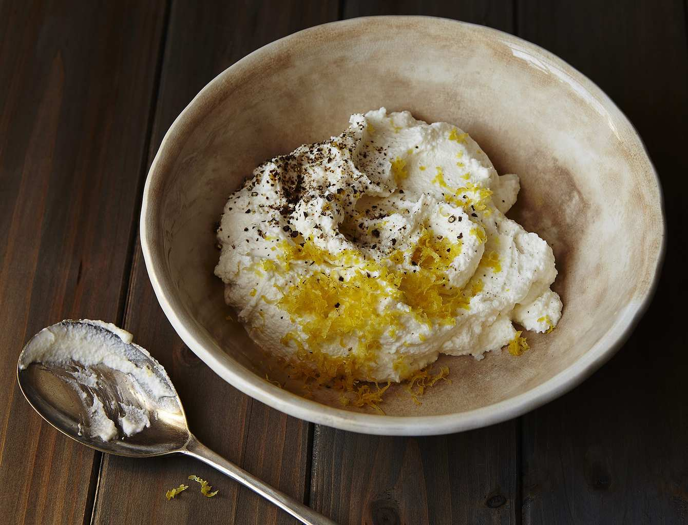 Ricotta cream with ingredients in rustic bowl with spoon on brown background