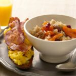 Close up of Cracked Wheat Cereal with Bacon and Egg Toasts on metallic plate