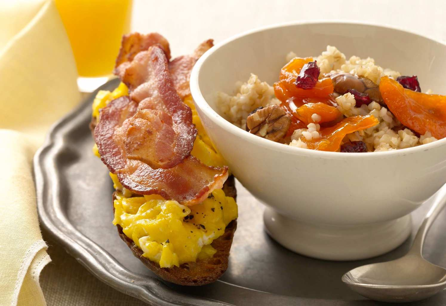 Cereal and fruit in white bowl with bacon egg toast on pewter plate cropped