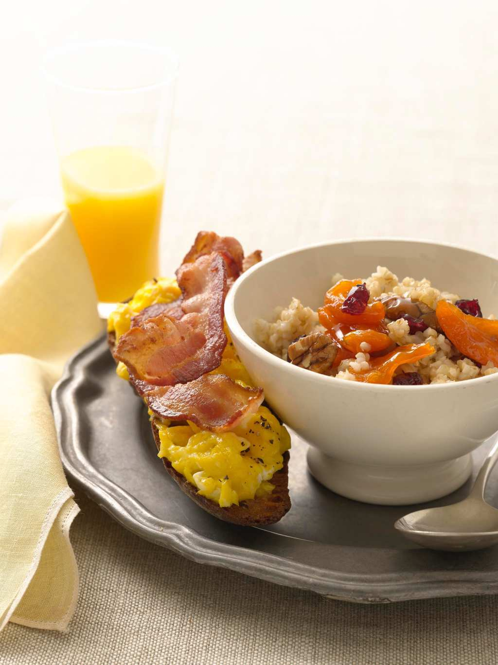 Cereal and fruit in white bowl with bacon and egg toast on pewter plate w yellow napkin