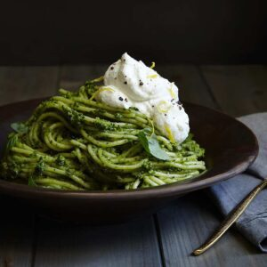 Fresh green pesto pasts in brown bowl with lemon cream