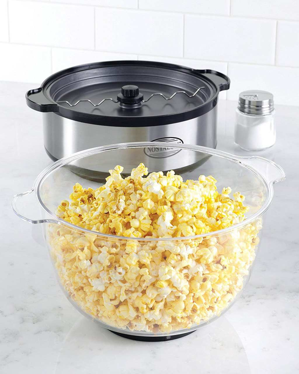Bowl of popcorn with popper and salt.
