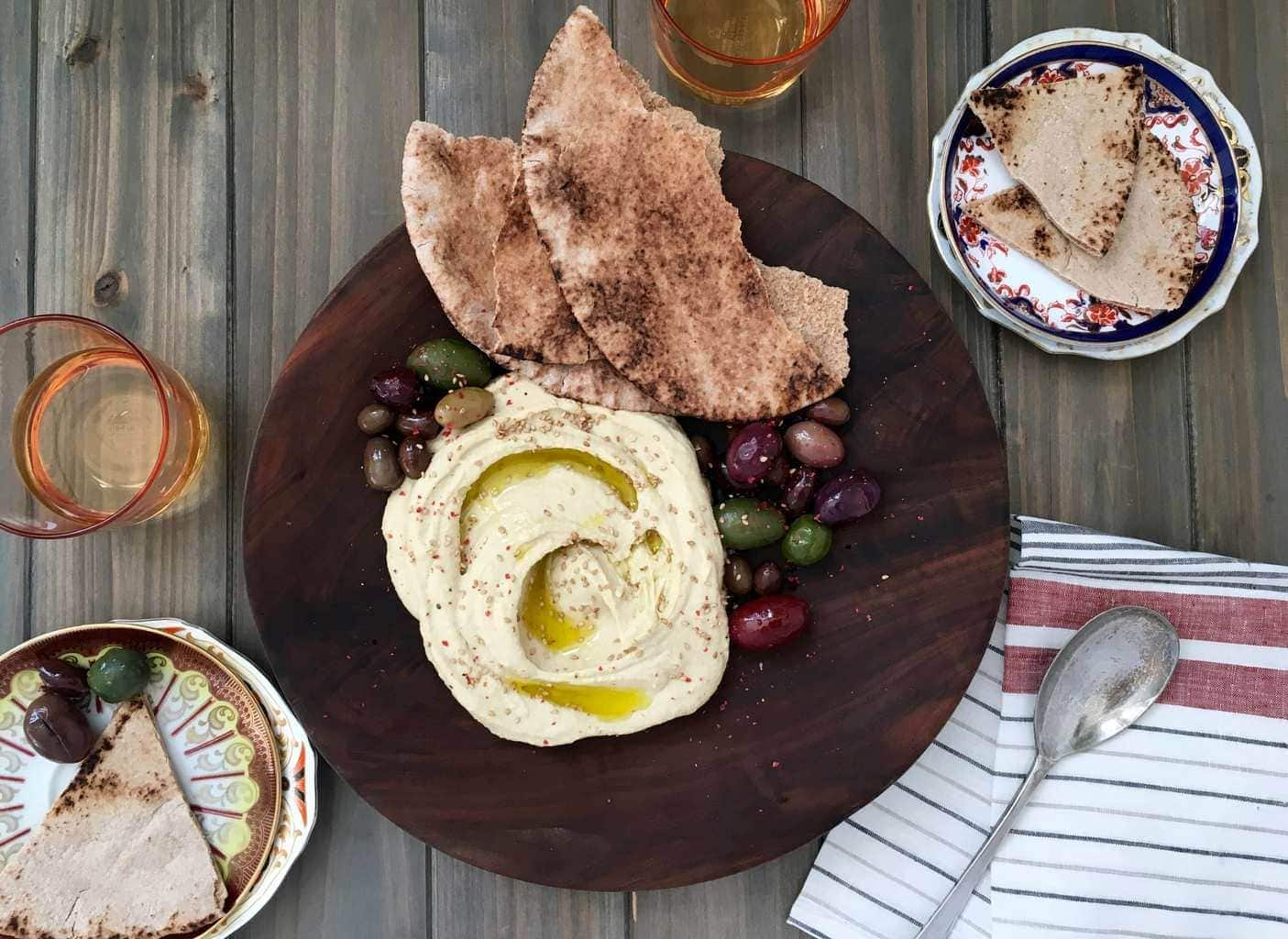 Hummus, olives, naan on wooden plate.