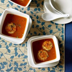 two bowls with tomato soup and cheese dumplings